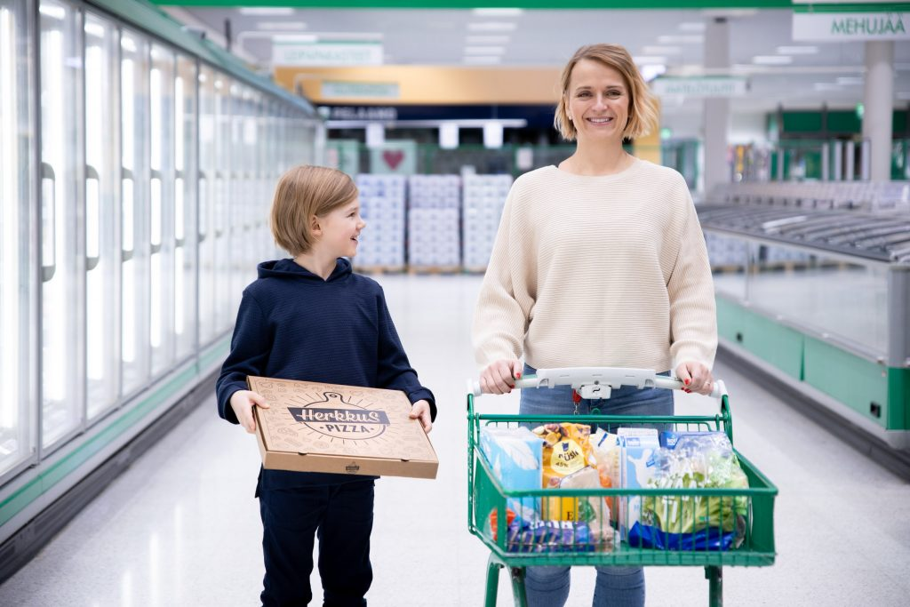 Äiti ja poika Prismassa ostoksilla, pojalla kädessä HerkkuS-pizzalaatikko. Kuva: Antti Haataja