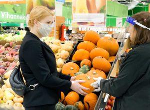 Nainen kaupassa kasvomaski kasvoillaan ojentamassa myyjälle kurpitsaa.