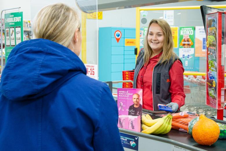 Nainen palvelee asiakasta hymyillen Salen kassalla