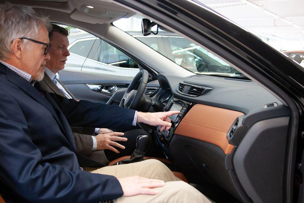 Autotalo Ripatin myyjä neuvoo asiakkaalle auton ominaisuuksia